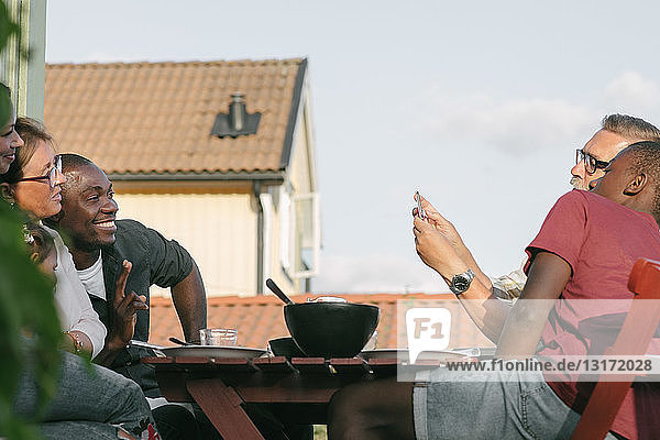 Älterer Mann fotografiert Familie  die am Tisch auf der Veranda sitzt