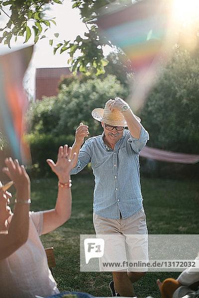 Ältere Frau klatscht  während ein Mann einen Strohhut trägt und an einem sonnigen Tag im Garten spazieren geht