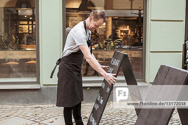 Mittlerer erwachsener Besitzer arrangiert Tafel vor dem Laden
