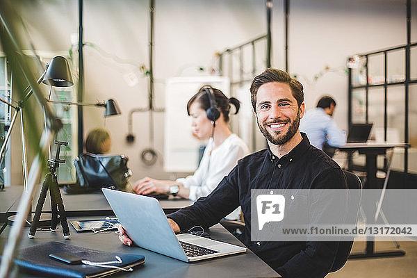 Porträt eines selbstbewussten Geschäftsmannes mit Laptop am Schreibtisch im Kreativbüro
