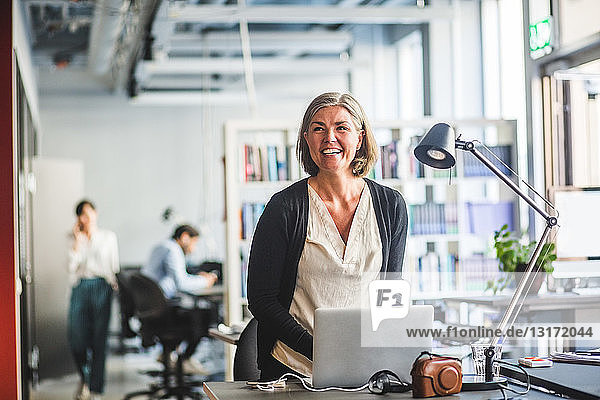 Glückliche kreative Geschäftsfrau schaut weg  während sie im Büro am Schreibtisch steht