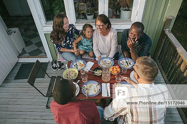 Hochwinkelaufnahme einer Mehrgenerationen-Familie beim Mittagessen am Tisch auf der Veranda