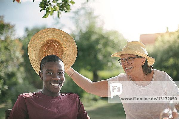 Glückliche Großmutter hält Strohhut über Enkel während Gartenparty an sonnigem Tag