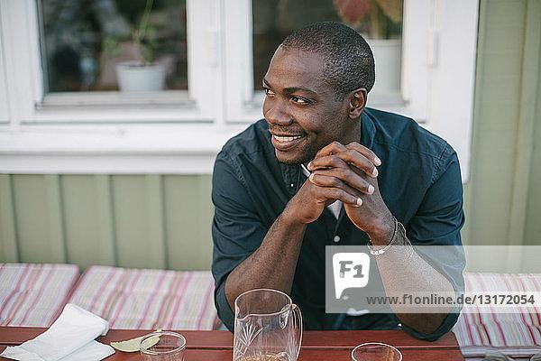 Lächelnder mittelgroßer erwachsener Mann schaut weg und sitzt am Tisch auf der Veranda