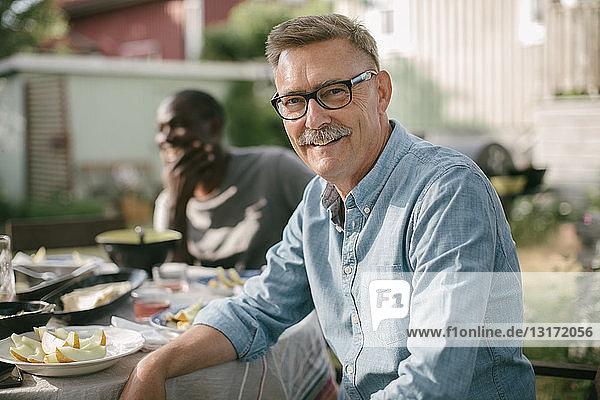 Porträt eines lächelnden älteren Mannes  der während einer Gartenparty am Tisch sitzt