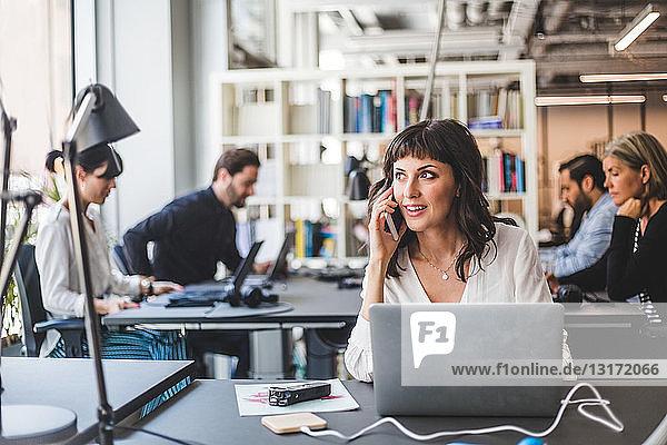 Geschäftsfrau schaut weg  während sie am Schreibtisch im Kreativbüro mit dem Handy telefoniert