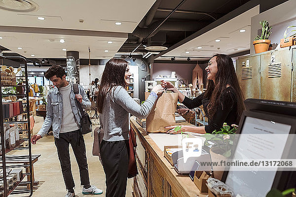 Smiling saleswoman giving merchandise to customer at checkout counter