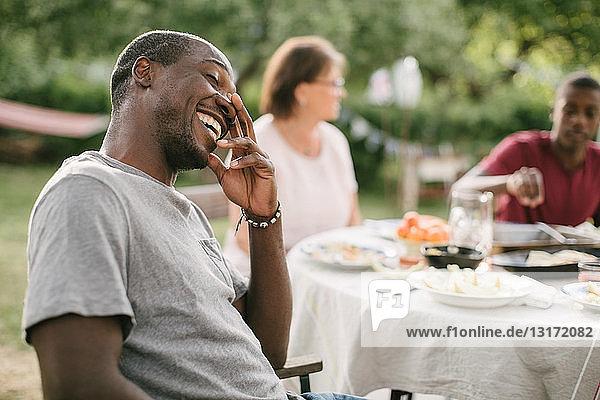 Mittelgroßer erwachsener Mann lächelt  während er während einer Gartenparty am Tisch sitzt