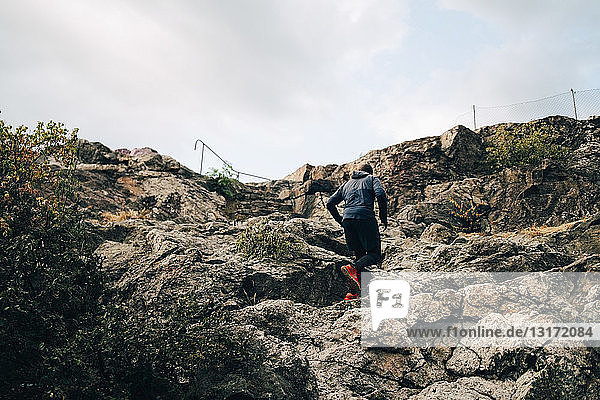 Low angle view of sportsman climbing rocks on hill