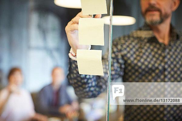 Mittelteil eines Geschäftsmannes  der auf einen Haftzettel schreibt  der im Kreativbüro auf Glas geklebt wird