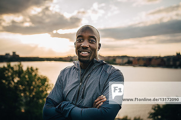 Portrait of confident male athlete standing on hill against sky during sunset