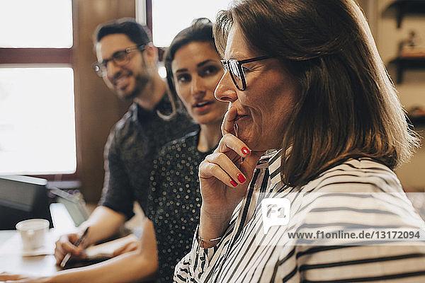 Nachdenkliche reife Geschäftsfrau von Kollegen während der Diskussion im Amt