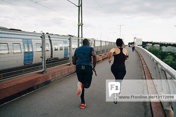 Rear view of male and female athletes running on footbridge in city