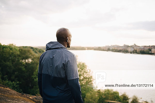 Male athlete looking at sea while standing on hill against sky