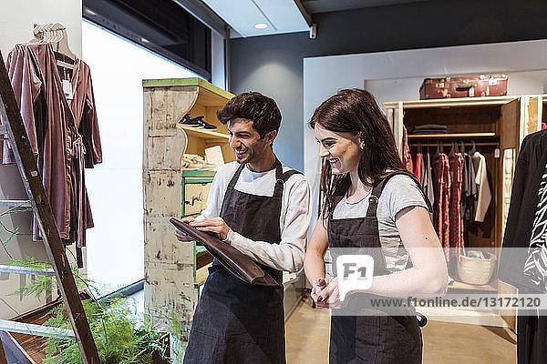 Lächelnde männliche und weibliche Kollegen  die während der Arbeit im Geschäft Ordner überprüfen