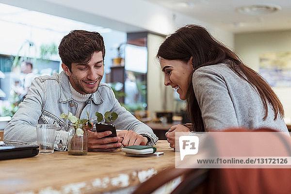 Lächelnde männliche und weibliche Freunde schauen auf das Smartphone im Cafe