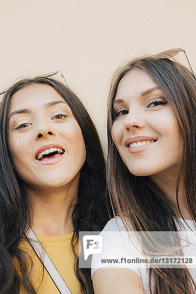 Portrait of happy young friends standing against wall