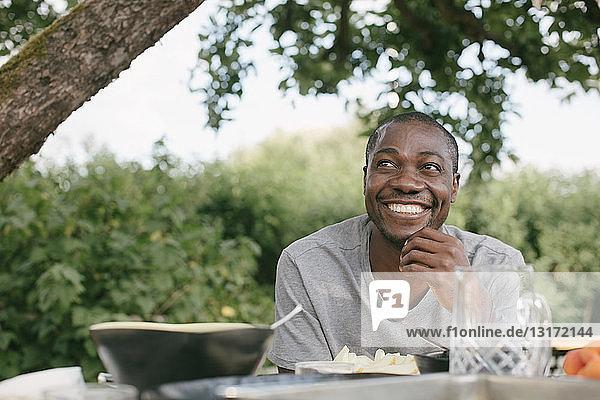 Lächelnder mittelgroßer erwachsener Mann schaut weg und isst während der Gartenparty am Tisch