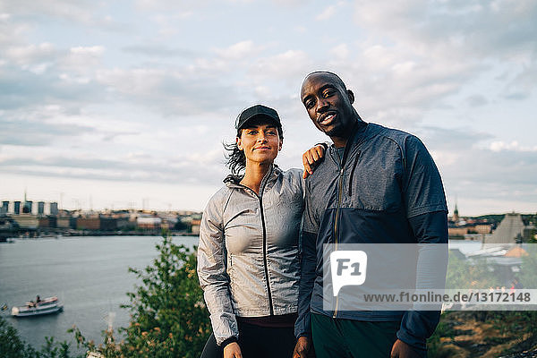 Portrait of confident male and female athlete standing on hill against sky