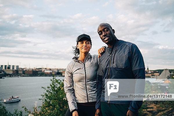 Porträt eines selbstbewussten Sportlers und einer selbstbewussten Sportlerin  die auf einem Hügel gegen den Himmel stehen