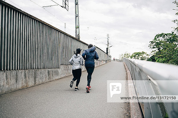Rear view of male and female athlete jogging on footbridge in city
