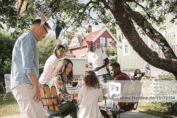 Familie sieht Mädchen an  das während einer Gartenparty im Garten am Tisch steht