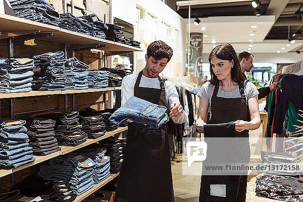 Verkäufer diskutiert mit Mitarbeiter über Jeans im Geschäft