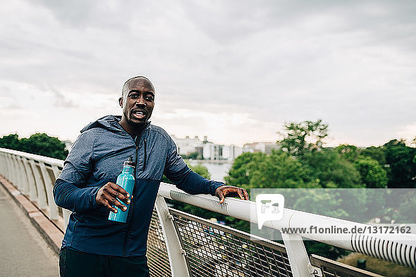 Portrait of thirsty sportsman holding water bottle while standing by railing on footbridge against sky