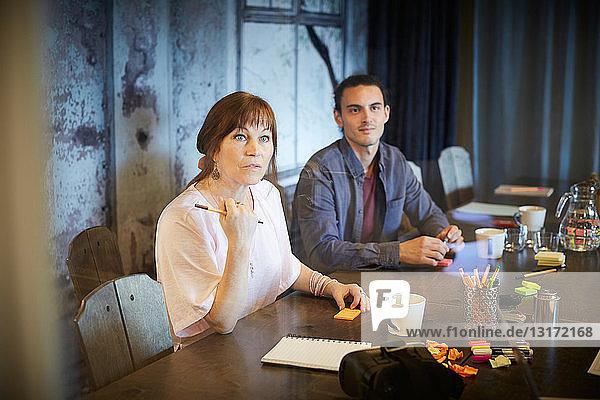 Kreative Geschäftsleute schauen weg  während sie im Büro am Konferenztisch sitzen