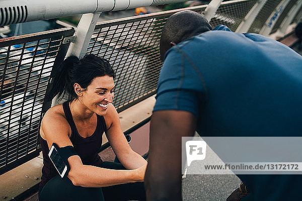Female athlete showing mobile phone to sportsman on footbridge