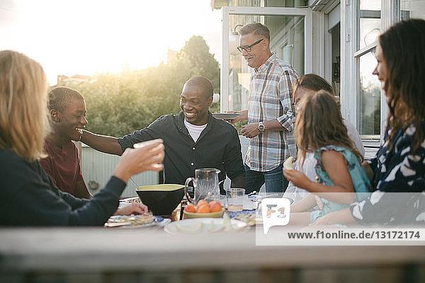 Fröhliche Mehrgenerationen-Familie genießt Mittagessen auf der Veranda