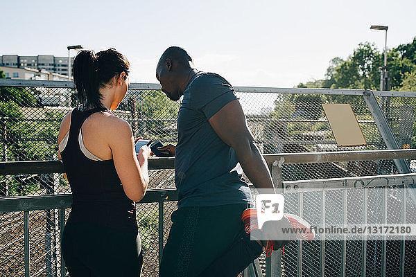 Female athlete showing mobile phone to man stretching leg by railing on bridge