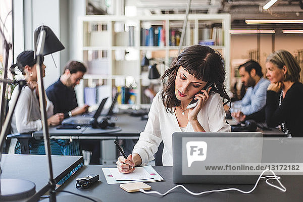 Businesswoman talking on mobile phone while working at desk in creative office