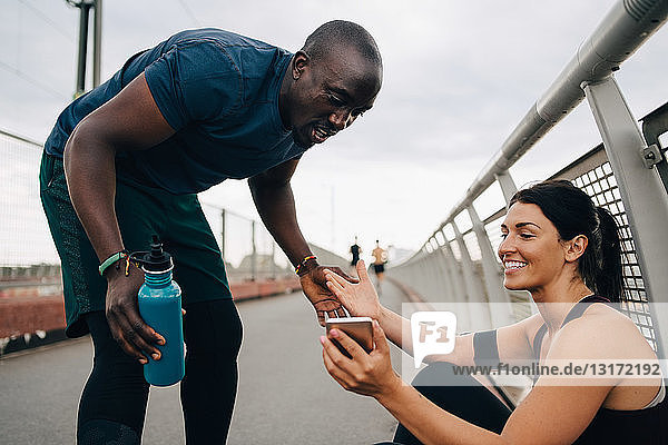 Female athlete smiling while showing mobile phone to sportsman on footbridge