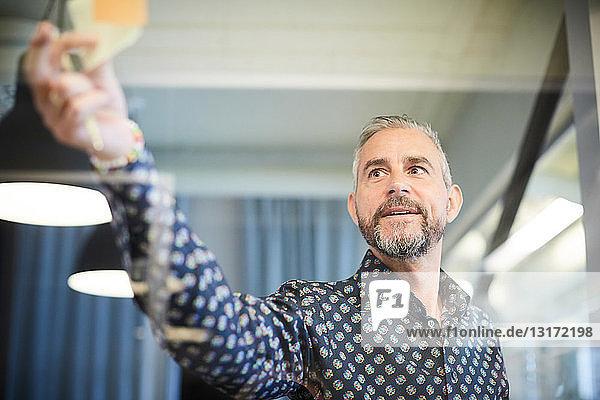 Reifer Geschäftsmann klebt Haftnotiz auf Glas im Sitzungssaal