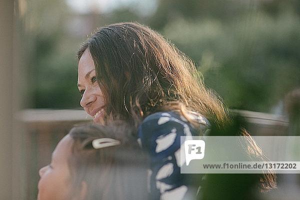 Lächelnde Frau mittleren Alters schaut weg  während sie mit ihrer Tochter auf der Veranda sitzt