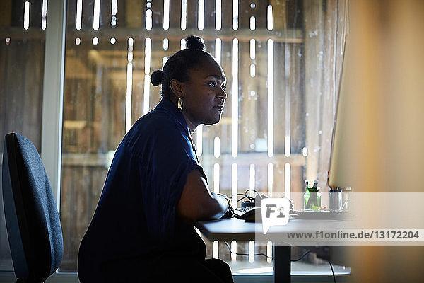Seitenansicht einer kreativen Geschäftsfrau  die am Computerschreibtisch im Büro arbeitet