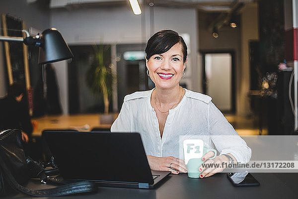 Portrait of confident businesswoman holding coffee mug while sitting at desk in office