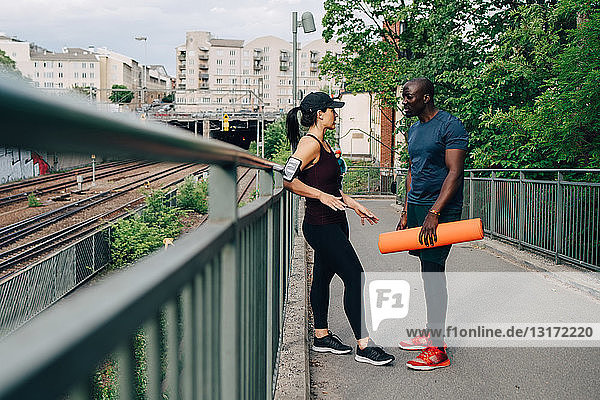 Sportsman holding yoga mat while talking with female athlete on footbridge in city