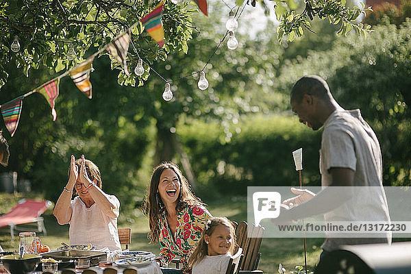 Fröhliche Mehrgenerationen-Familie mit Mittagessen am Tisch im Hinterhof während der Gartenparty