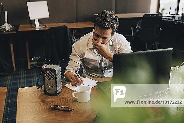 Geschäftsmann bedeckt Mund beim Schreiben in Papier am Büroschreibtisch