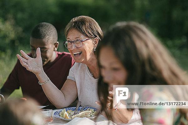 Glückliche ältere Frau beim Mittagessen mit der Familie im Garten während einer Gartenparty