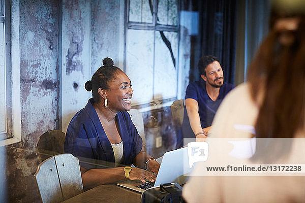 Kreative Geschäftsfrau lächelt  während sie bei einer Besprechung mit Kollegen im Büro den Laptop benutzt