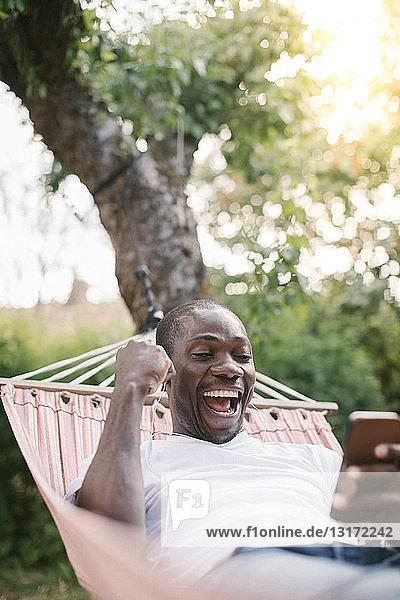 Fröhlicher mittelgroßer Mann schaut auf Handy  während er sich auf einer Hängematte im Hinterhof entspannt