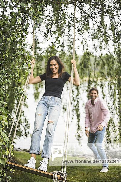 Fröhliche Frau schwingt auf Seilschaukel  während ein männlicher Freund am Seeufer steht Fröhliche Frau schwingt auf Seilschaukel, während ein männlicher Freund am Seeufer steht