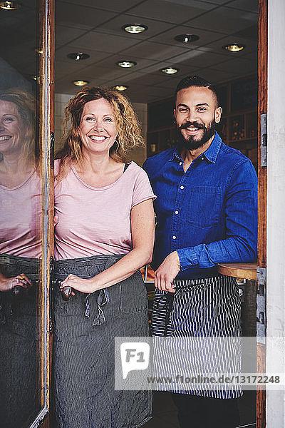 Porträt von lächelnden Kollegen  die am Eingang des Geschäfts stehen
