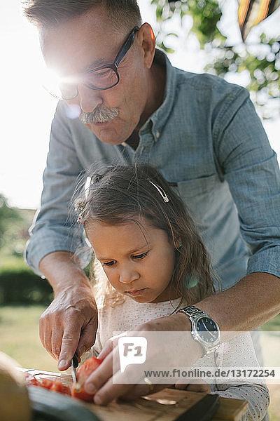 Großvater lehrt Enkelin  Tomaten bei Tisch im Hinterhof zu schneiden