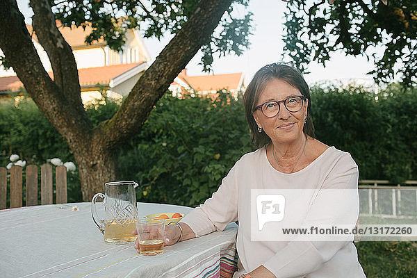 Porträt einer lächelnden Frau  die ein Getränk in der Hand hält  während sie im Hinterhof am Tisch sitzt