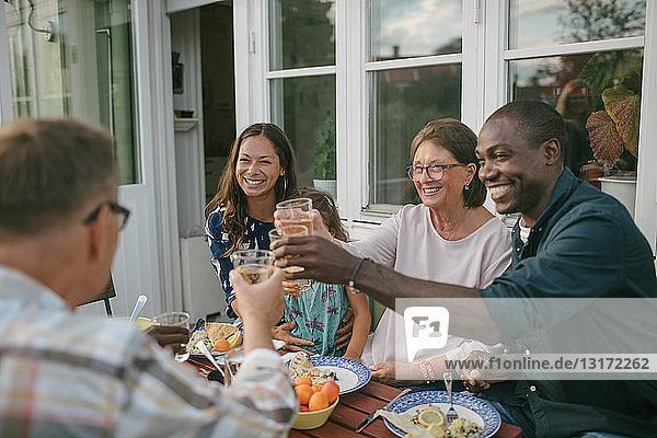 Fröhliche Mehrgenerationen-Familie stößt während der Gartenparty am Tisch auf Getränke an