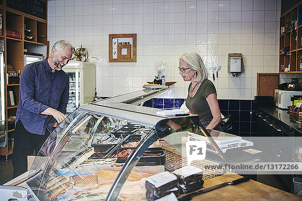 Customer smiling while showing seafood at retail display to saleswoman in deli